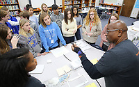 NWA Democrat-Gazette/DAVID GOTTSCHALK George Moncrief (right), a coach with Moncrief Game Changer Entrepreneurship Summit, describes to eighth grade honor student at Central Junior High School, Monday, December 3, 2018, equipment used for a print business  during the summit at the school in Springdale. The summit, sponsored by the Schmieding Foundation, featured workshops that included written expression, sales skills and first impression development.