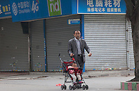 A man pushes a baby in a stroller past shuttered shops at the edge of the Yue Yuen Industrial Holdings Limited factory in Dongguan, Guangdong Province, China, 03 March 2015.
