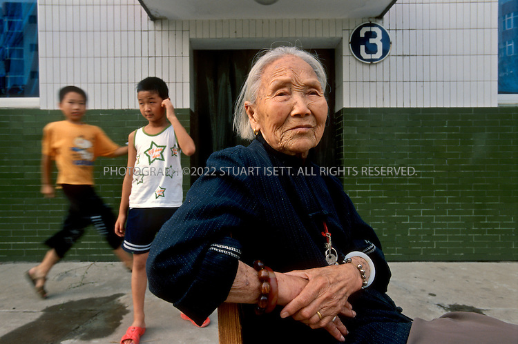 "7/15/2005--Nanjie Village, Henan Province, China..Zhang Shui Qin (90) and her two grandsons (behind) live in Nanjie village, a model communist village in the central province of Henan, in a free apartment which is completely furnished by the communist collective. Nanjie collectivised its agricultural production and industry in the mid 1980s - when the rest of the country was doing the opposite, introducing market reforms put forward by former leader Deng Xiaoping. Although the teachings of the ""Great Helmsman"" serve as the moral compass for the 3,100 people of Nanjie, the real secret to its collective well-being is, well, capitalist: two dozen village enterprises manufacturing all sorts of things ? noodles, beer, pharmaceuticals. One even promotes ""red tourism.""..It continues to be run on Maoist egalitarian lines and has become something of a tourist attraction because of its staunch adherence to the values of the past. .Photograph By Stuart Isett.All photographs ©2005 Stuart Isett.All rights reserved."