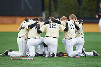 Members of the Wake Forest Demon Deacons huddle up prior to the game against the Marshall Thundering Herd at Wake Forest Baseball Park on February 17, 2014 in Winston-Salem, North Carolina.  The Demon Deacons defeated the Thundering Herd 4-3.  (Brian Westerholt/Four Seam Images)