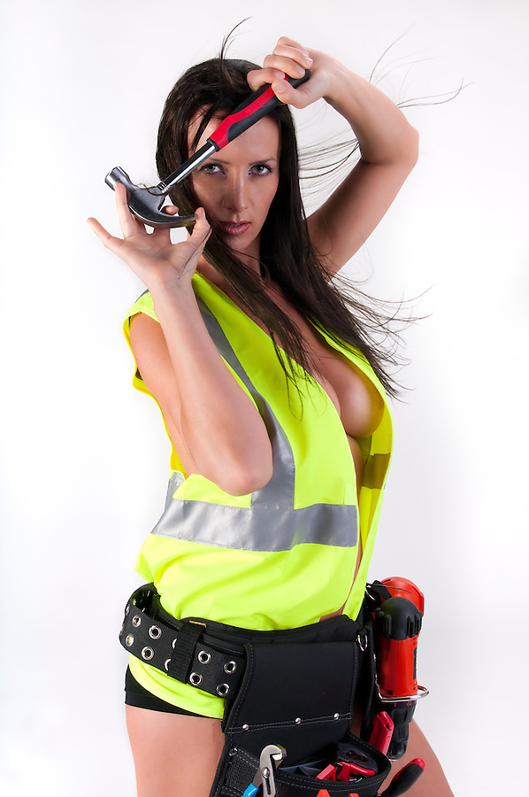 Very sensual woman with safety vest and hammer. All logos removed.