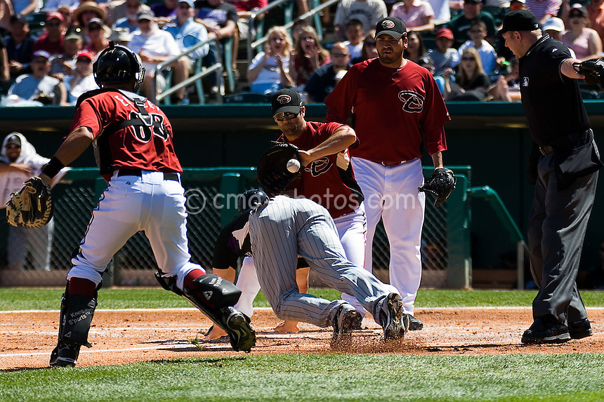 Mar 22, 2008; Tucson, AZ, USA; Colorado Rockies left fielder Matt Holliday (5) avoids a tag from Arizona Diamondbacks catcher Ed Easley (68) in a rundown and slides safely home before Arizona Diamondbacks first baseman Conor Jackson (34) can apply a tag as Arizona Diamondbacks pitcher Edgar Gonzalez (31) looks on during a game between the Colorado Rockies and Arizona Diamondbacks at Tucson Electric Park. The Rockies would win the game 12-11.