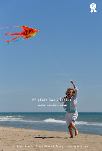 Girl (8) flying kite on beach (Licence this image exclusively with Getty: http://www.gettyimages.com/detail/83154257 )