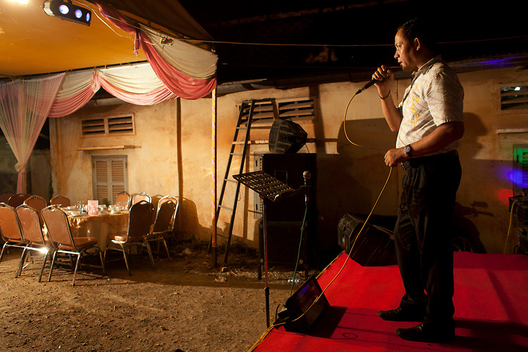 A wedding guest sings karaoke to empty seats at buddhist wedding in a small village outside of Phnom Penh, Cambodia. <br /> <br /> Photos &copy; Dennis Drenner 2013.