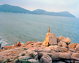 CHINA, Putou Shan, an elevated view of monk standing on a rock near Thousand Steps Beach