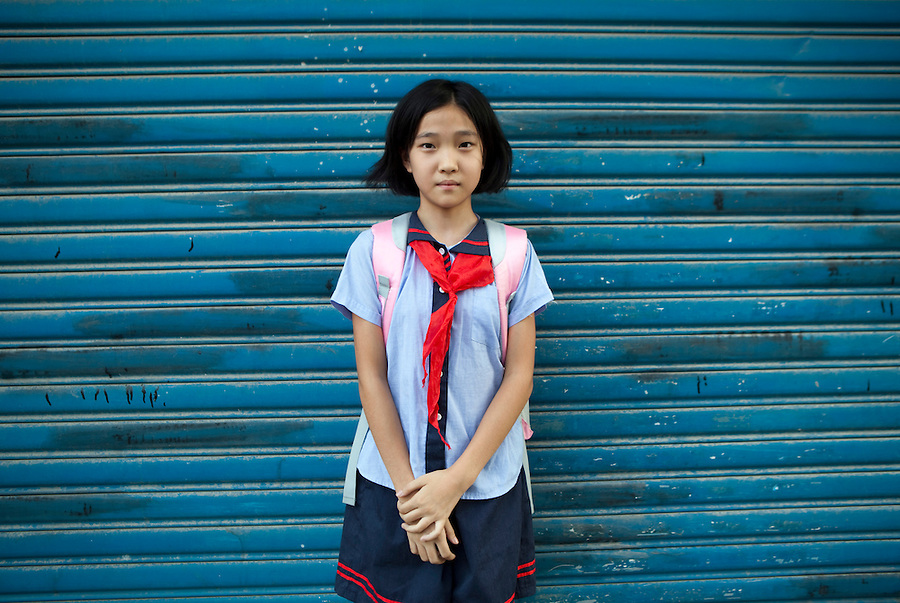 """A young school girl, wearing her """"young pioneer"""" red scarf, walking home from school."""