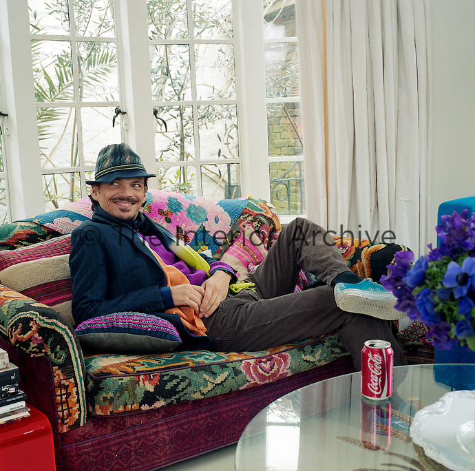 Portrait of fashion designer Matthew Williamson reclining on the sofa at his London home