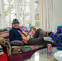 Portrait of fashion designer Matthew Williamson reclining on the sofa at his London home