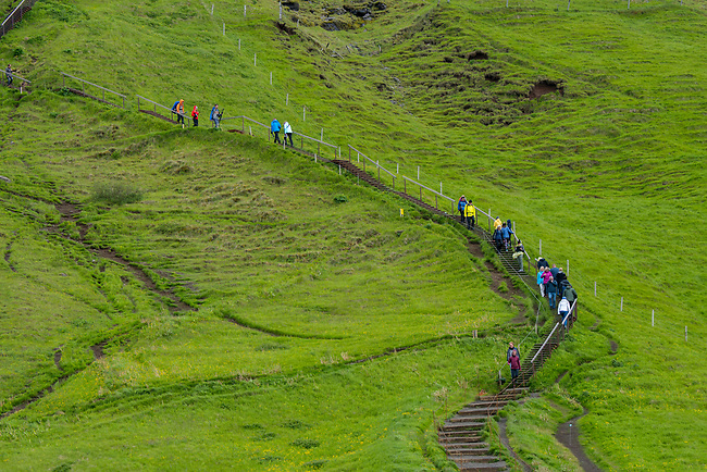 Tourists hiking up the hill next to the Skogafoss, which is one of the biggest waterfalls in southern Iceland with a width of 15 meters (49 feet) and a drop of 60 m (200 ft).