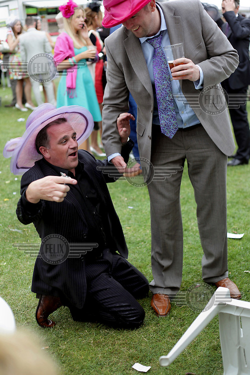 A man wearing a woman's hat falls to his kneels during the Royal Ascot race meeting. The annual event, during which each day begins with the Queen's arrival in a horse drawn carriage, dates back to 1711 when Queen Anne organised the first races on what was then a heath near Windsor Castle.
