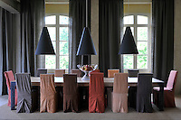 The dining table is 4 metres long and surrounded by chairs in loose linen covers in varying earth tones