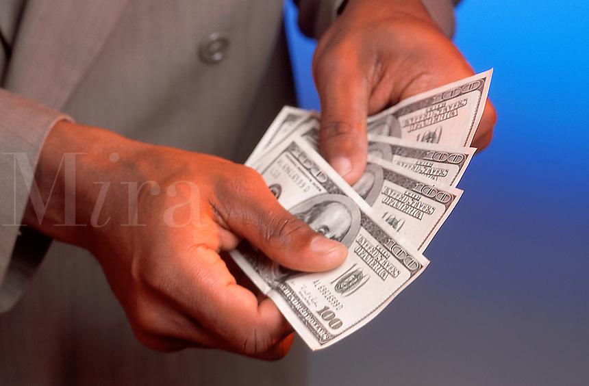 Hands holding $100 dollar bills.