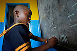 A boy writes on a blackboard during class in a day care center in Monrovia, Liberia, sponsored by United Methodist Women.