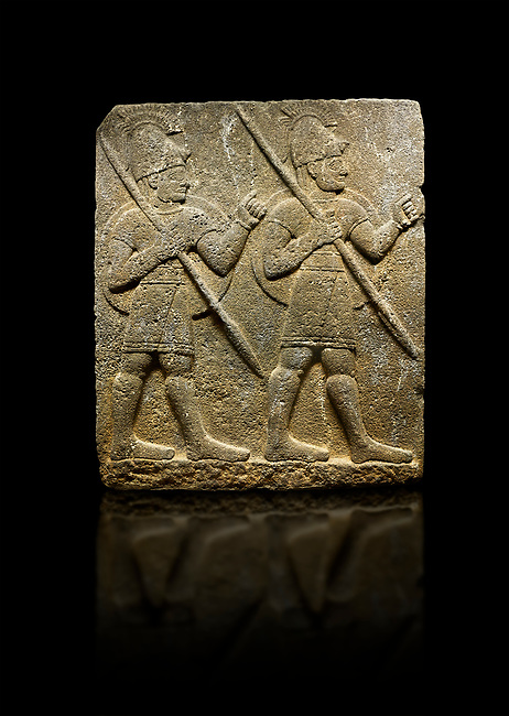 Photo of Hittite monumental relief sculpted orthostat stone panel from the Herald's Wall. Basalt, Karkamıs, (Kargamıs), Carchemish (Karkemish), 900-700 B.C. Military parade with soldiers. Anatolian Civilisations Museum, Ankara, Turkey<br /> <br /> Two helmeted soldiers marching soldiers in short skirts carry the shield on their backs and the spears in their hands.  <br /> <br /> Against a black background.