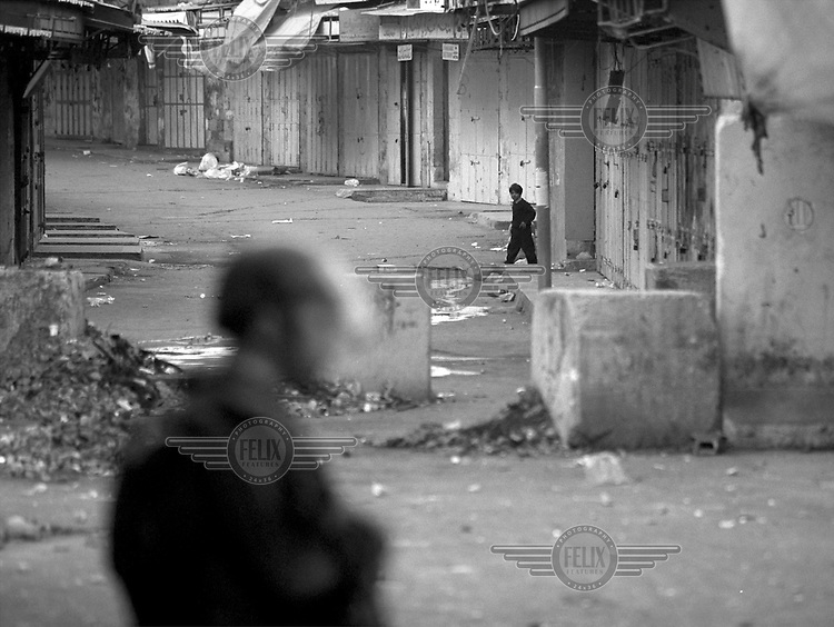 A boy peeks out during a curfew following clashes in the center of Hebron, Palestine.