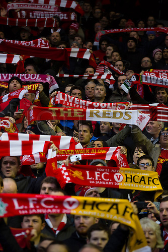01.01.2014 Liverpool, England. Fans in The Kop holding scarfs aloft while singing You'll Never Walk Alone, before the Premier League game between Liverpool and Hull City from Anfield.