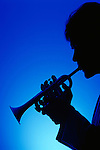 Silhouette of a man playing the trumpet with a blue background .