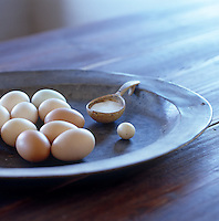 A plate of eggs and a small wooden spoon filled with salt