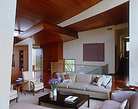 The mahogany-clad roof in this elegantly furnished living room curves upwards towards the glazed walls on one side of the room