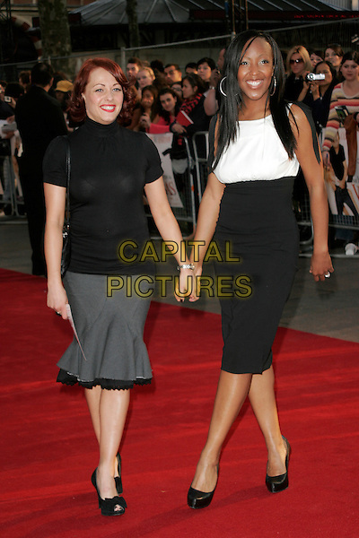"SARAH CAWOOD & ANJELLICA BELL.World premiere of ""What Happens In Vegas"" held at the Odeon Leicester Square, London, England. .April 22nd 2008 .full length Sara black top grey gray skirt fishtail black shoes peep toe bows polo neck turtleneck white sleeveless angelica anjelica holding hands .CAP/AH.©Adam Houghton/Capital Pictures."