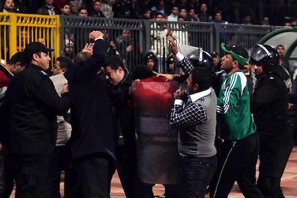 POR03.PORT SAID (EGIPTO).1/2/2012.-Policías y aficionados egipcios se enfrentan en el estadio de Port Said, Egipto, hoy miércoles 1 de febrero de 2012. Al menos 73 personas han muerto y 136 han resultado heridos han resultado heridas por los enfrentamientos entre las hinchadas de dos equipos de fútbol egipcios en Port Said (noreste), según informó a Efe el delegado de Sanidad de la ciudad, Helmy Ali al Atny.Al Atnye explicó que la mayoría de fallecidos perdieron la vida por fracturas en el rostro y por hemorragias internas, y también hubo un gran número de ingresados por caídas desde los graderíos del estadio, donde se enfrentaban el Al Ahli, de El Cairo, y el equipo local, Al Masri.EFE/STRINGER