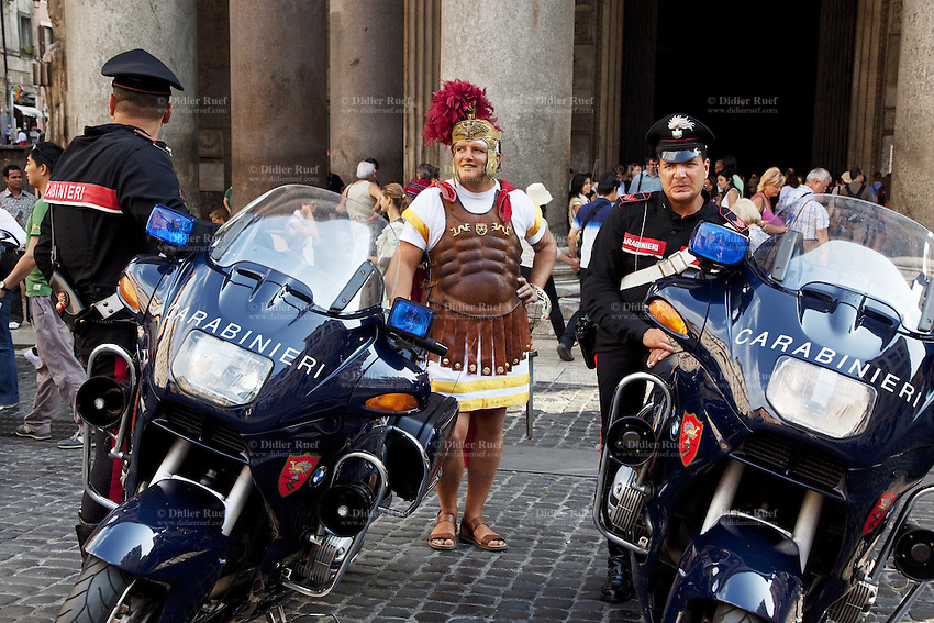 "Italy. Lazio region. Rome. The Pantheon. Filip Ionut, a romanian citizen, is dressed as an antique roman soldier. He is standing between two policemen from the Carabinieri forces with their motorcycles. Filip Ionut is working with the tourist industry and daily poses for pictures with individuals tourists in front of the entrance of the Pantheon. The Pantheon is a building, commissioned by Marcus Agrippa as a temple to all the gods of Ancient Rome, and rebuilt by Emperor Hadrian in about 126 AD. The building is circular with a portico of three ranks of huge granite Corinthian columns (eight in the first rank and two groups of four behind) under a pediment. A rectangular vestibule links the porch to the rotunda, which is under a coffered, concrete dome. The Pantheon is one of the best preserved of all Roman buildings. It has been in continuous use throughout its history, and since the 7th century, the Pantheon has been used as a Roman Catholic church dedicated to ""St. Mary and the Martyrs"" but informally known as ""Santa Maria Rotonda"". The square in front of the Pantheon is called Piazza della Rotonda. Romanian immigration.  26.09.2011 © 2011 Didier Ruef"