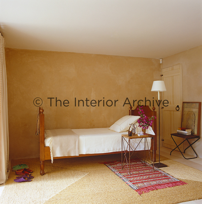 Simple single bedroom with unpainted plaster walls