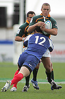 South African centre Stefan Watermeyer is tackled by Yann David during the Division A U19 World Championship clash at Ravenhill.