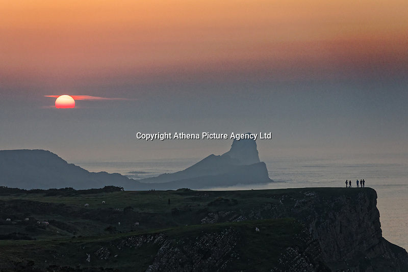 The sun sets over Worm's Head in Rhossili, Wales, marking the end of another unusually warm day. Wednesday 27 February 2019
