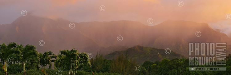 A passing rain shower on Kauai is lit up orange by the setting sun.  Namolokama and the Hanalei mountains are seen as the backdrop.