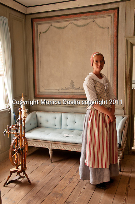 A volunteer in period costume at the Skogholm Manor at Skansen in Stockholm, the outdoor museum of traditional Swedish buildings and farmsteads