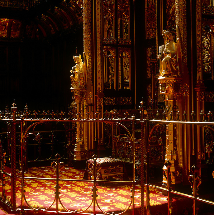 The dais, on which the monarch's throne sits, is surrounded by a gilded canopy of carved panelling and a wrought metal balustrade