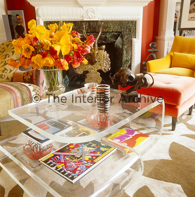 Placed on an acrylic coffee table in a cantilevered design a large flower arrangement accentuates the red and yellow colour scheme of the living room