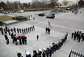 A U.S. military honor guard team carries the flag draped casket of former U.S. President George H. W. Bush from the U.S. Capitol December 5, 2018 in Washington, DC. A funeral service will be held today for former U.S. President Bush at the Washington National Cathedral. President Bush will be buried at his final resting place at the George H.W. Bush Presidential Library at Texas A&M University in College Station, Texas. A WWII combat veteran, Bush served as a member of Congress from Texas, ambassador to the United Nations, director of the CIA, vice president and 41st president of the United States. <br /> Credit: Win McNamee / Pool via CNP