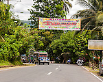 A jeepney leaves Sampaloc on the road to Lucban, leaving town under a banner welcoming visitors to the annual Bulihan Fiesta in April 2012.  (Sampaloc, Quezon Province, the Philippines)