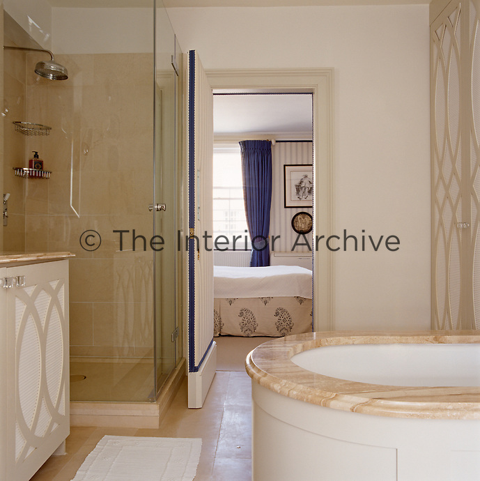 The guest bathroom has a marble-topped bath and a glass-enclosed shower while the door to the bedroom is lined in fabric