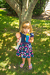 Toddler with doll baby and zippy cup under tree in summer.