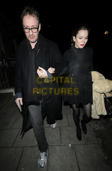 """DAVID THEWLIS & ANNA FRIEL.Leaving after the evening performance of """"Breakfast At Tiffany's"""", Theatre Royal Haymarket, London, England..January 6th, 2010.full length black coat dress tights walking arms linked couple carrying fur silver grey gray trainers sneakers .CAP/CAN.©Can Nguyen/Capital Pictures."""