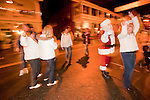 A group of women dance with Santa Claus on the street at the end of Sutter Creek's annual Parade of Lights Christmas parade downtown on a rainy night in the  Mother Lode of Calif.
