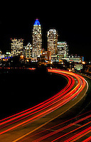 Uptown Charlotte skyline at night featuring the Bank of America headquarters crown lit in blue light in Charlotte, NC. Car's red break lights are shown streaking along interstate 277 John Belk Freeway.