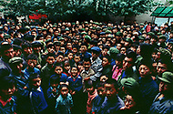 September, 1985. Shaanxi Province, China. People in the streets of Yan'an. Photographer Jean Pierre Laffont in the middle of the crowd with his camera.