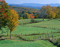 Caledonia County, VT<br /> Meandering fencelines in green meadows with distant rolling hills and White Mountains in fall color