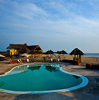 The kidney-shaped swimming pool is situated on the beach in front of a series of thatched sunshades