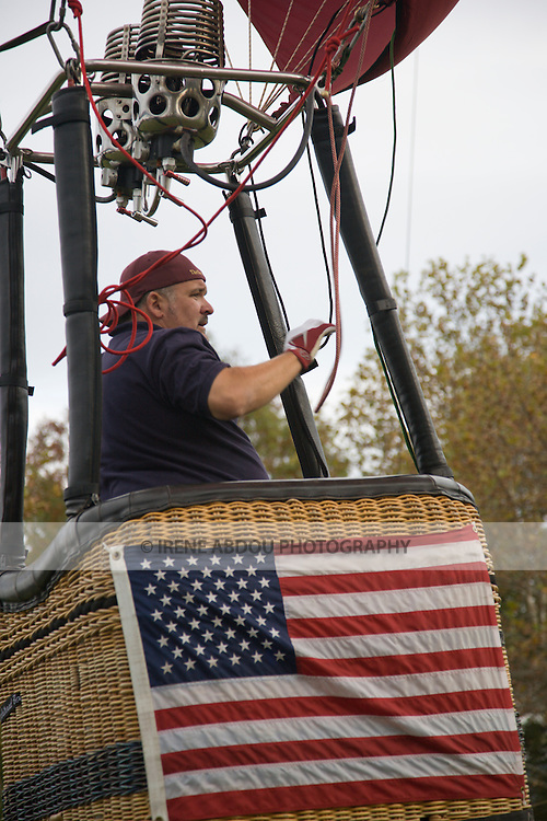 A hot air balloonist prepares to float upwards at the 2008 Shenandoah Valley Hot Air Balloon Festival at Historic Long Branch in Millwood, Virginia .