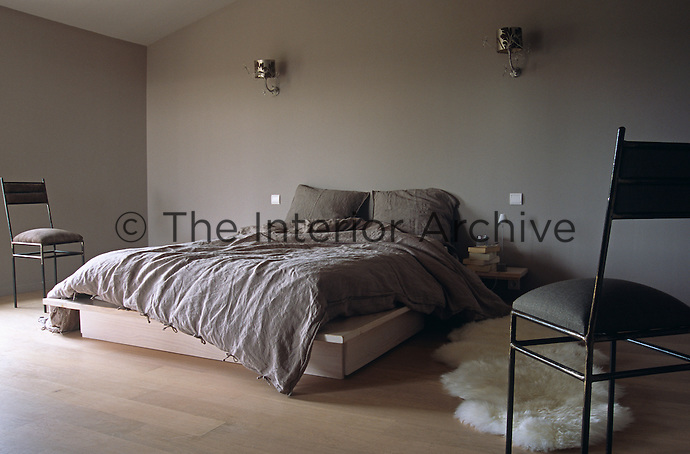 Natural coloured bed linen on the platform bed reflects the overall colour scheme of the bedroom