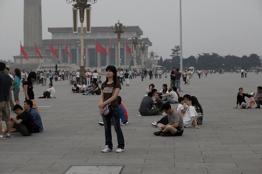 Fin de journée sur la place Tiananmen. Une jeune fille seule té debout , propbablment une des dizaines de policiers en civils qui scrutent chaque mouvement sur la place. Au fond, le monument aux héros de la révolution, à l'arrière plan le mausolée de Mao.