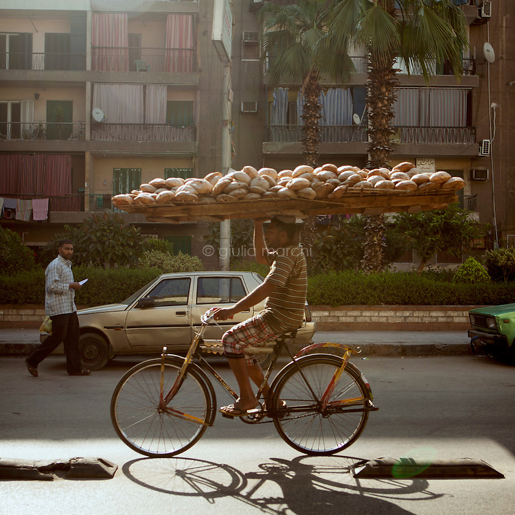 Egypt / Cairo / 21.5.2013 / Street scene in Cairo: a man rides a bicycle while carrying on his head the bread to sell.