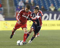 Toronto FC forward Luis Silva (11) passes the ball as New England Revolution midfielder Juan Carlos Toja (7) defends. In a Major League Soccer (MLS) match, the New England Revolution (blue) defeated Toronto FC (red), 2-0, at Gillette Stadium on May 25, 2013.