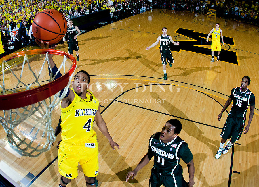 Michigan guard Darius Morris (4) makes a basket, with Michigan State guard Keith Appling (11) watching, in the second half of an NCAA college basketball game, Saturday, March 5, 2011, at Crisler Arena in Ann Arbor. Michigan won 70-63. (AP Photo/Tony Ding)