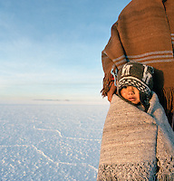 Portrait of young boy in traditional dress on Salar de Uyuni salt flats, Bolivia. The Salar de Uyuni are the worlds largest salt flats.